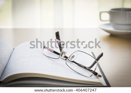 Eyeglasses put on a book with on the desk, 