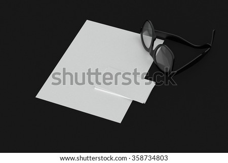 Eyeglasses with blank white paper and business card with copy space for your brand or text lying on a black background, high angle view. 3d Rendering. - stock photo