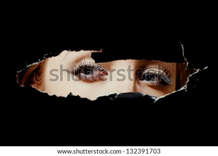 Eyes of a young woman peeping through a hole - stock photo