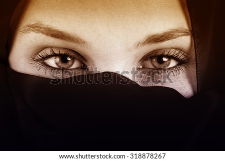 Eyes of arab woman with veil over face - stock photo