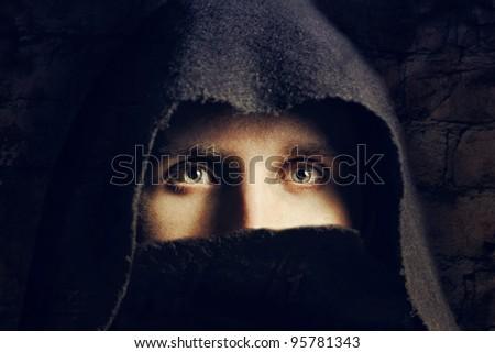 Eyes of man in black hood - stock photo