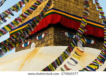 Eyes of the Buddha with prayer flags at Boudhanath Stupa on Apr 19th before the earthquake - stock photo