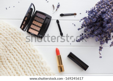 Eyeshadow, brushes and lipstick in autumn / winter colors viewed from the top on a wooden table - stock photo