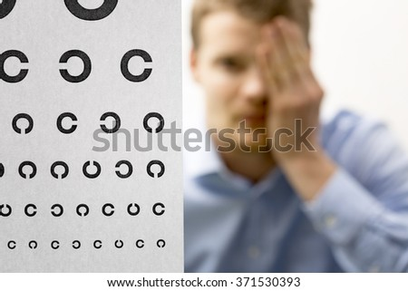 eyesight check. male patient under eye vision examination. focus on test chart - stock photo