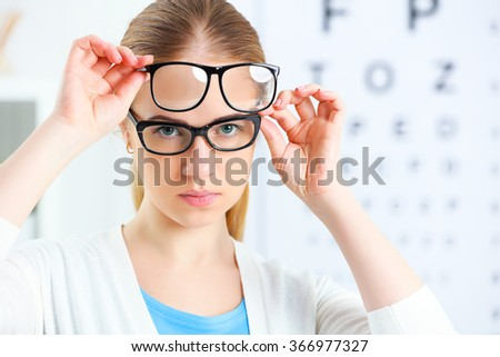 eyesight check. woman choose glasses at the doctor ophthalmologist optician - stock photo