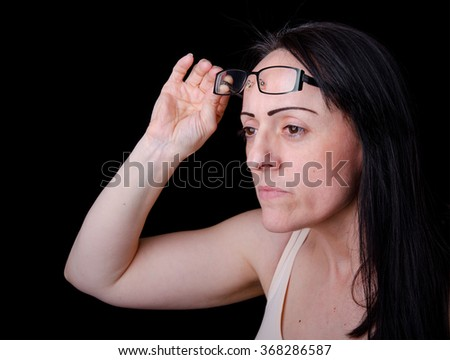 Eyesight, woman lifting her glasses to focus. Black background with copy space. - stock photo
