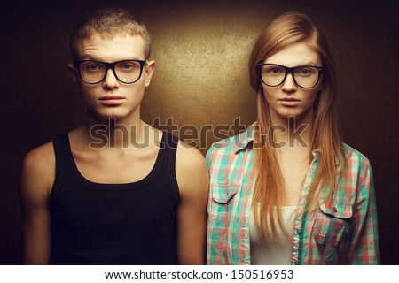 Eyewear concept. Funny portrait of gorgeous red-haired (ginger) fashion twins in casual shirts wearing trendy glasses and posing over golden background. Hipster style. Close up. Studio shot - stock photo