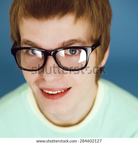 Eyewear concept. Portrait of fashionable young man with stylish haircut wearing trendy glasses & posing over blue background. Perfect hair & skin. Hipster style. Close up. Studio shot - stock photo
