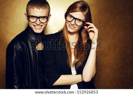 Eyewear concept. Portrait of gorgeous red-haired twins in black clothes wearing trendy glasses & posing over golden background together & smiling. Natural make-up. Copy-space - stock photo