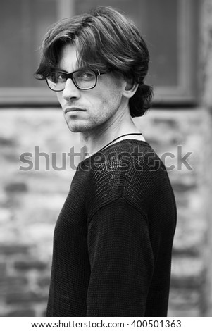 Eyewear concept. Portrait of romantic charismatic man wearing stylish eyeglasses. Close up. Urban, street style. Monochrome, black and white outdoor shot. - stock photo