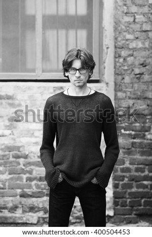 Eyewear, street fashion concept. Portrait of romantic charismatic man wearing stylish eyeglasses. Monochrome, black and white outdoor shot. - stock photo