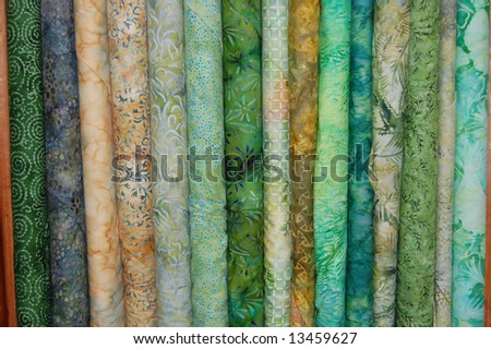 Fabric bolts - green batik prints - stock photo