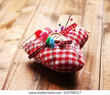 Fabric heart with color pins and safety pins on wooden background - stock photo