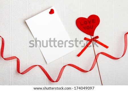 Fabric Love You heart with an empty postcard and a red ribbon on - stock photo