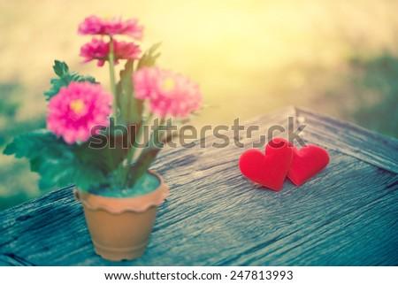 Fabric valentine heart on grunge wood table with gebera flower foreground.. Retro filter. - stock photo