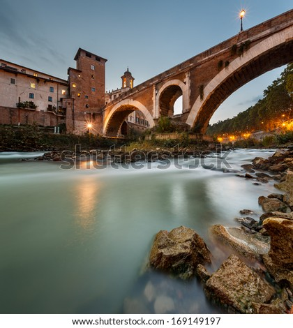 Fabricius Bridge and Tiber Island at Twilight, Rome, Italy.  This is the oldest Roman bridge in Rome, still existing in its original state from 62 BC, built by Lucius Fabricius. - stock photo