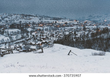 Fabulous mountain village in winter during snowfall, fairy tale landscape - stock photo