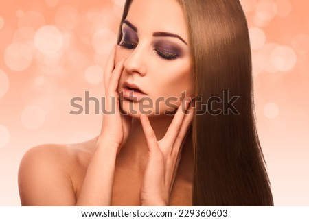 Fabulous portrait of lovely woman with perfect straight brown hair in studio on abstract orange background - stock photo