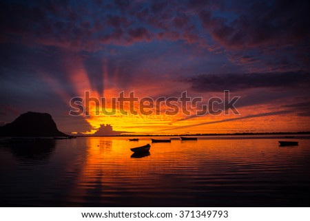 fabulous view of the sunset in Mauritius. Fishing boats on the background of mountains and the setting sun - stock photo