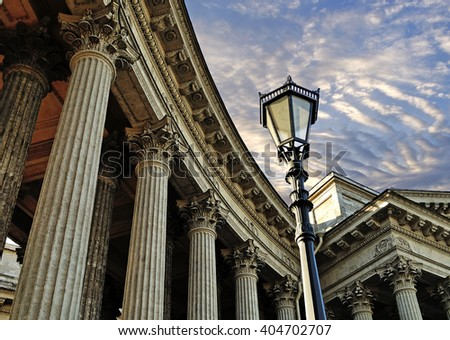 Facade details of Kazan Cathedral in Saint Petersburg, Russia - colonnade and metal lantern against dramatic sunset sky - stock photo