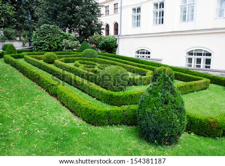 Facade of a building with a beautiful garden in front of it. - stock photo