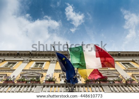 Facade of an ancient building with italian and european flag, against a blue sky and clouds. - stock photo