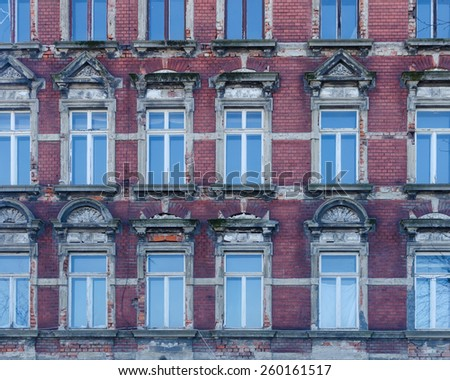 facade of an old abandoned building with windows reflecting the blue sky - stock photo