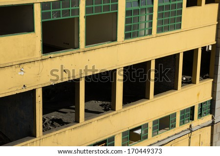 Facade of an old and abandoned yellow urban building. - stock photo