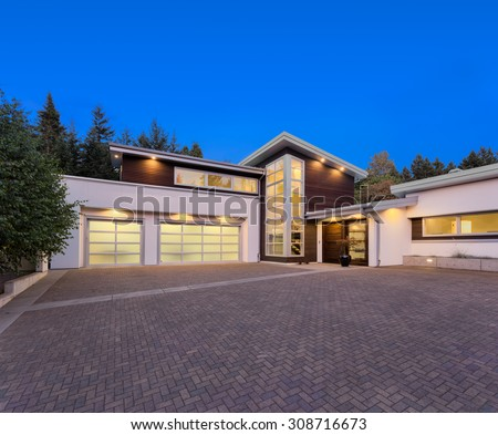 Facade of large, luxury home with expansive driveway with colorful sunset backdrop - stock photo