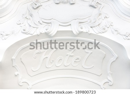 facade of luxury hotel and hotel sign on a plain white wall with ornaments - stock photo