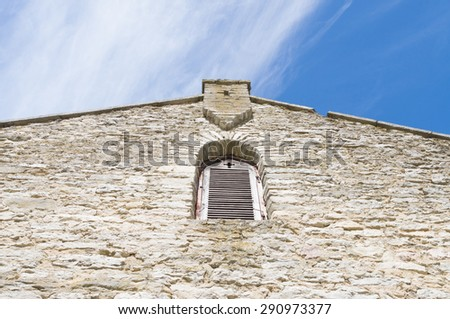 Facade of medieval church with window and cross shape in wall - stock photo