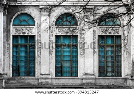 Facade of old abandoned building with three large arched windows of blue glass and columns. Monochrome background - stock photo