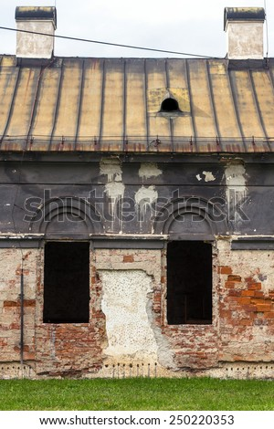 Facade of old abandoned historic house in the district of the city of Zilina in Slovakia. House with three dark empty windows and beautiful architecture - stock photo