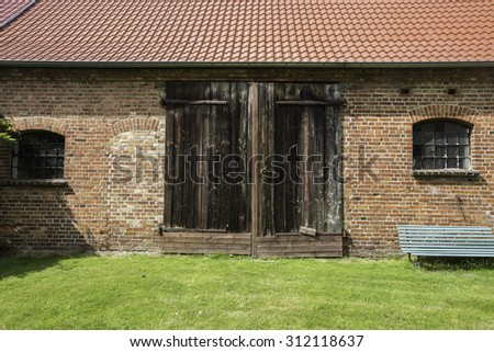 Facade of Old brick walls barn with tiled roof, and wooden door - stock photo