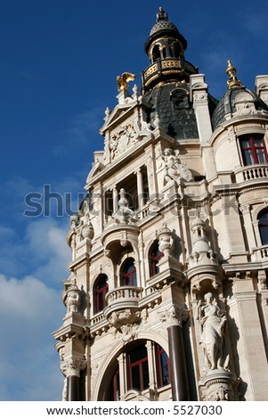 Facade of old building in Europe, richly decorated with gold, statues and carvings. Taken against a blue sky in Antwerp, Belgium. - stock photo