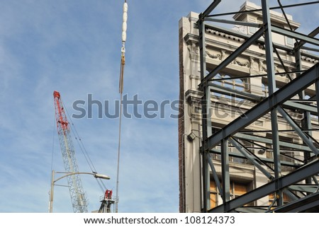 Facade of the historical building facade without building, crane, hook and blue sky in background, new building constructed in Melbourne, Australia - stock photo