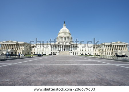 Facade of the US Capitol Building in Washington DC USA view from stone plaza under blue sky - stock photo