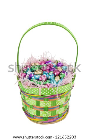 Facade shot of a green basket with colorful chocolate eggs inside isolated in a white background - stock photo