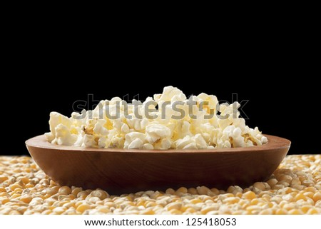 Facade shot of a plate of popcorn placed on top of corn grains against a black background - stock photo