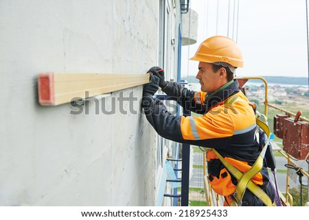Facade worker builder working with level at ventilation facade construction on a building - stock photo