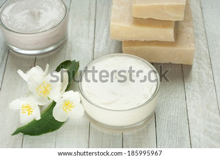 face and body cream moisturizers with jasmine flowers on white wooden - stock photo