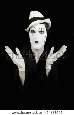 face and hands of mime with dark make-up on black background - stock photo