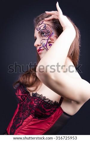 Face Art Concept: Portrait of Caucasian Female With Unique Face Art Painting. Posing In Corset Against Black.Vertical Image Orientation - stock photo