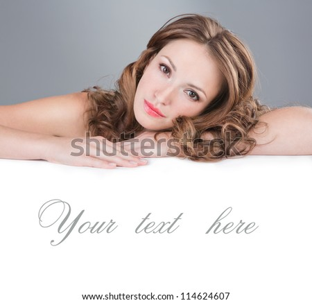 Face beauty skin care. Portrait of beautiful woman with a manicure, daily fresh make-up and wavy hairstyle.  Empty copy space for your text on banner. SPA. Horizontal. Grey background. Studio shot. - stock photo
