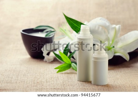 Face/body care concept: bottles of creams/lotions/serums with white lily flowers, closeup shot - stock photo