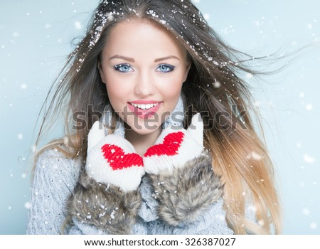 Face close up of beautiful happy young woman wearing winter gloves covered with snow flakes. Christmas snowing portrait concept.  - stock photo