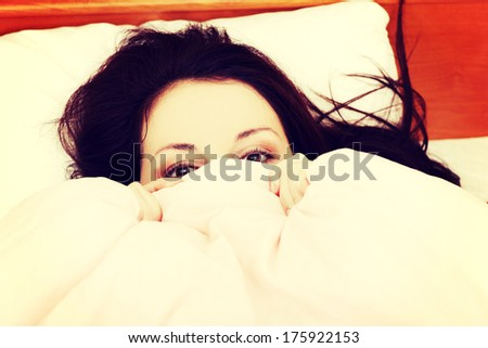 Face closeup of a beautiful young woman hiding her face under the sheet. - stock photo