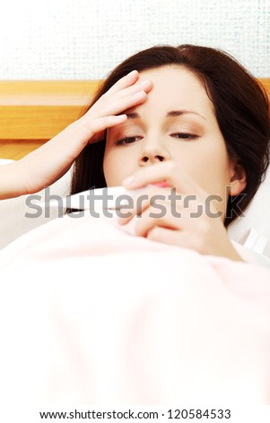 Face closeup of a beautiful young woman lying in bed during a cold, checking fever on thermometer, touching her forehead. - stock photo