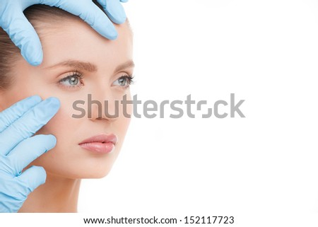 Face examining. Portrait of beautiful young woman looking away while hands in gloves examining her face - stock photo