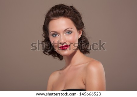 Face of a beautiful young brunette woman with bright lipstick and curly hair  - stock photo